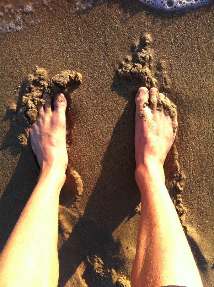 Med båda fötterna i sanden på stranden i slutet av dagen